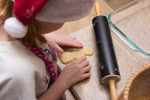 Girl Leaning Over Counter Top Making A Snowman Sugar Cookie With Rolling Pin