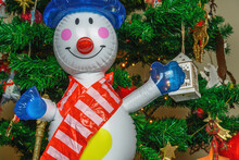 Large Inflatable Toy Snowman As Decoration On A Christmas Tree. Air Blown Seasonal Figure Before Illuminated Artificial Pine Branches With Lights And Colourful Decorations.