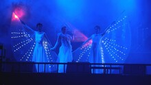 Group Of Dancers With White Dress Performance To Show On Stage With Spotlight Or Disco Lights. Some Of Their Dress Has Part Look Like Wings.