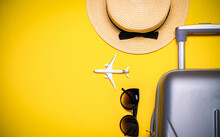 Sea Shells. Suitcase, Sunglasses With Palm Leaves And Straw Hat, White Plane In Travel Composition On Yellow Background. Road Frame Set. Flat Lay, Top View.