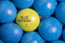 Blue Monday Text With Sad Smiley Face. One Yellow Candy In Blue. Most Depressing Day Of The Year. Blue Monday Concept. Influence Of The Environmen.