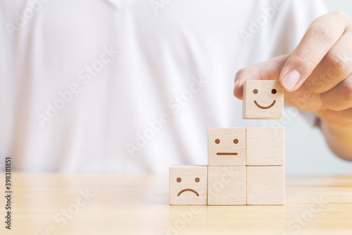 Fotografie, Obraz Hand chooses smiley face growth on wood block cube, The best excellent business
