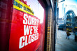 'Sorry We're Closed' sign in high street shop window- many shops are now closed due to the Covid 19 pandemic