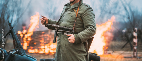 Leinwand Poster Re-enactor Dressed As German Wehrmacht Infantry Soldier In World War Ii Standing Against The Background Of A Burning House