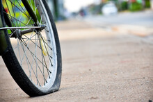 Rear Wheel Of Bike Which Is Flat And Parked On The Pavement Beside The Road.