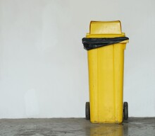 A Yellow  Trash Lie On One's Back Beside The Building Wall.