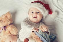 Happy Baby In Santa's Hat With Soft Toys