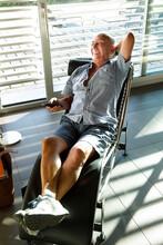 Anziano Settantenne Si Rilassa Su Una Poltrona Nel Salotto Di Casa Sua