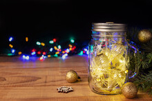 Golden Christmas Fairy Lights In Mason Jar On Wooden Table Against Dark Background, Space For Text