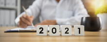 Cube Of Year Number 2021 On Wood Table With Businessman Working By Writing And Checking On Business Paper