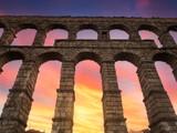 Fototapeta Nowy Jork - Bello atardecer en tonos anaranjados y azules, visto a través de los arcos del acueducto romano de Segovia, en Castilla y León,España