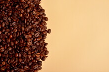Round Coffee Beans Stack On A Beige Background, Copy Space