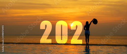 Fototapeta Happy New Year Card 2021. Silhouette lifestyle woman relax and freedom on sea beach in the sunset as Start up success 2021.  Holiday Concept, copy space and banner obraz