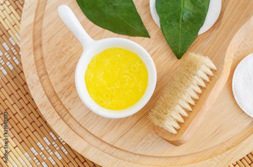 Fotografie, Obraz Homemade lemon fruit scrub (mask) in a small white bowl and wooden body brush
