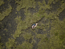 Girl Resting In Blue Dress On Green Moss And Black Lava Ground In Iceland In Drone Shot
