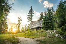 Isolated Cabin In Mountains Surrounded By Deep Forrest, Sunset In Background With Sunrays. Slovakia Tatra Mountains, Strbske Pleso.