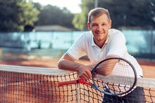 Portrait Of Positive Male Tennis Player With Racket Standing At Clay Court