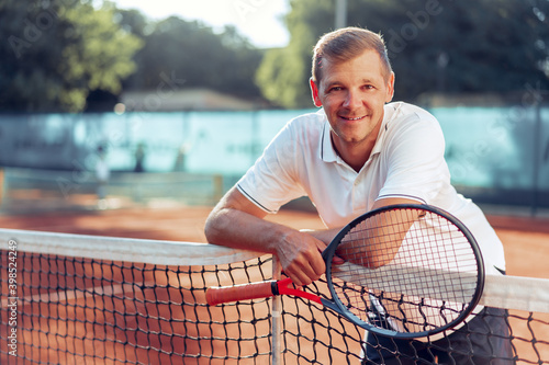 Obraz na plátně Portrait of positive male tennis player with racket standing at clay court