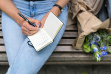 Midsection Of Woman Writing In Note Pad Sitting On Bench