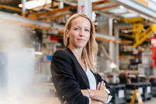 Confident Businesswoman With Arms Crossed Standing In Factory