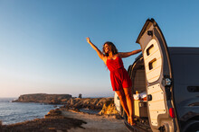Smiling Woman With Hand Raised Standing While Hanging On Camper Van Door At Beach