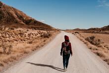 Spain, Navarre, Female Tourist Walking Along Empty Dirt Road In Bardenas Reales