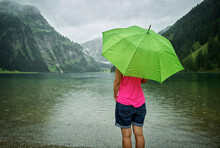 Mature Woman Standing With Green Umbrella At Vilsalpsee Lakeshore During Rainy Season