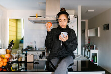 Teenage Girl Wearing Headphone Holding Apple While Using Mobile Phone At Home