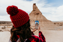 Spain, Navarre, Female Tourist Taking Smart Phone Photos Of Sandstone Rock Formation In Bardenas Reales