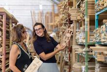 Interior Designer Choosing Ornate Design Of Wood Panel While Standing In Factory