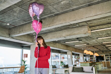 Businesswoman Holding Balloons While Standing In Loft Office