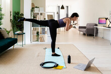 Young Female Athlete With One Leg Up Standing On Exercise Mat At Home