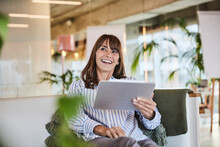 Happy Woman Using Digital Tablet While Sitting At Modern Home