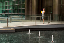 Businesswoman Talking Through Smart Phone While Walking On Footpath By Fountain In City