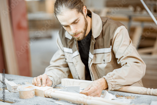 Papel de parede Manual worker finishing wooden products, spackling and grinding baluster at the
