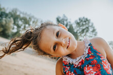 Little Girl Smiling While Standing At Beach