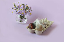 Colored Eggs In A Package With A Light Feather On The Background Of A Bouquet Of Delicate Flowers, Pastel Background, Space For Text