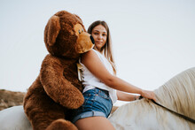 Portrait Of Beautiful Young Woman Riding Horse With Large Teddy Bear Behind