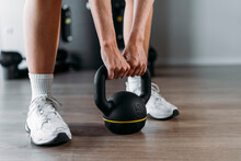 Close-up Of Woman Lifting Kettle Bell While Standing In Gym
