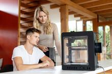 Team Examining 3D Printer At Home