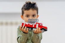 Cute Boy Holding Fire Engine Toy At Home