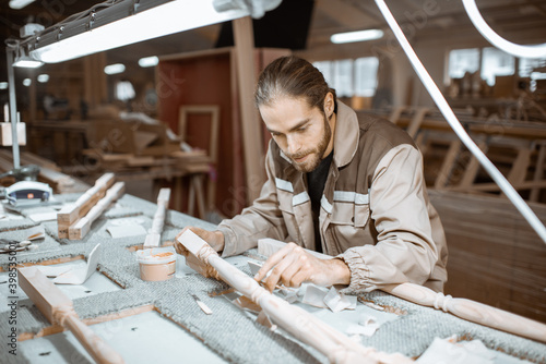 Fotografia Manual worker finishing wooden products, spackling and grinding baluster at the