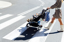 Mother With Son In Baby Carriage On Crosswalk In City During Sunny Day