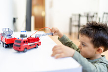 Boy Playing With Fire Engine Toy At Home