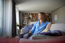 Smiling Woman Looking Away While Sitting On Sofa At Home