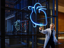 Male Cardiologist Light Painting Heart In Laboratory At Hospital