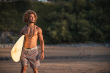 Shirtless Young Man With Surfboard Looking Away While Walking At Beach During Sunset