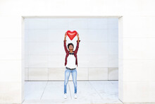 Young Woman Holding Aloft Red Heart Shape Balloon Against White Wall