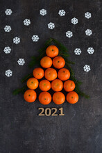 Creative Christmas Tree Made Of Oranges, Tangerines On Grey Background. Holiday-cards. Merry Christmas. Wooden Numbers 2021