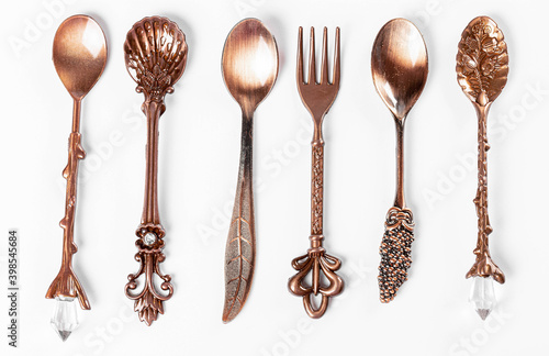 Fototapeta Coppers teaspoons and fork with decorated on handles ornament, top view